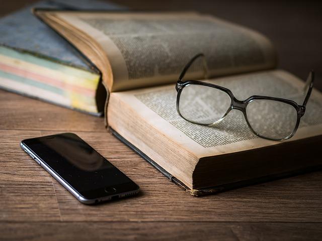 brýle na knize u mobilu